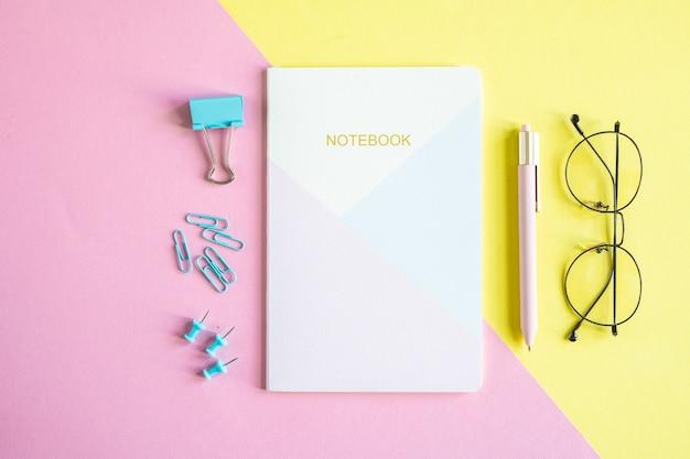 Kilka szpilek, klips, notatnik, długopis i okulary na różowym i żółtym tle