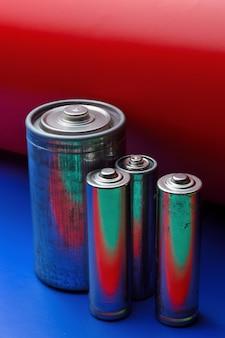Kilka wielokolorowych baterii na niebiesko-czerwonym tle. zbliżenie.
