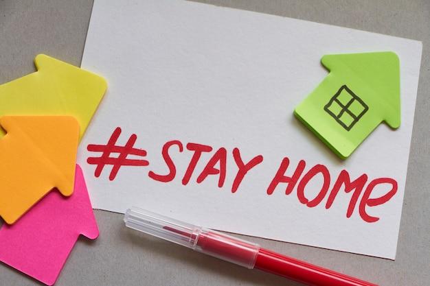Kilka wielokolorowych domów z papieru z hashtagem stay home i czerwonym znacznikiem. koncepcja stay at home.