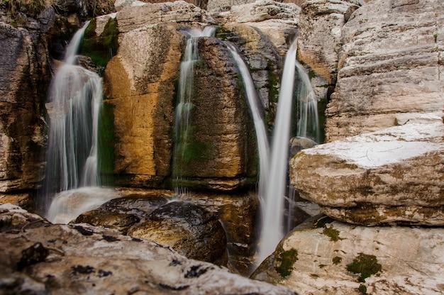 Kilka wodospadów spływających z wysokiej skały w kanionie martvili