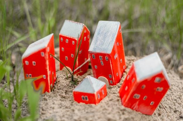 Kilka zabawek czerwone drewniane domy na piasku w zielonej trawie. koncepcja zakupu nieruchomości.