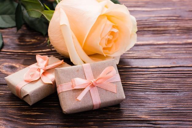 Kilka zapakowanych prezentów i świeża róża na drewnianym stole
