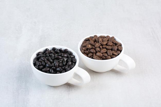 Kilka ziaren kawy i krople czekolady w filiżankach. zdjęcie wysokiej jakości