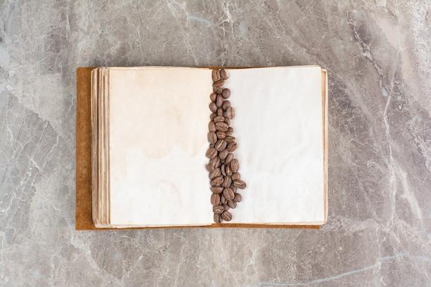 Kilka ziaren kawy na otwartej księdze. zdjęcie wysokiej jakości