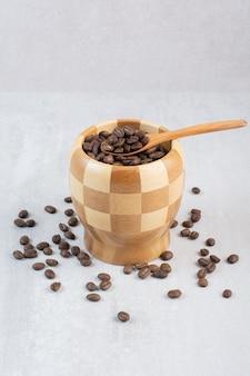 Kilka ziaren kawy w drewnianej misce z łyżeczką