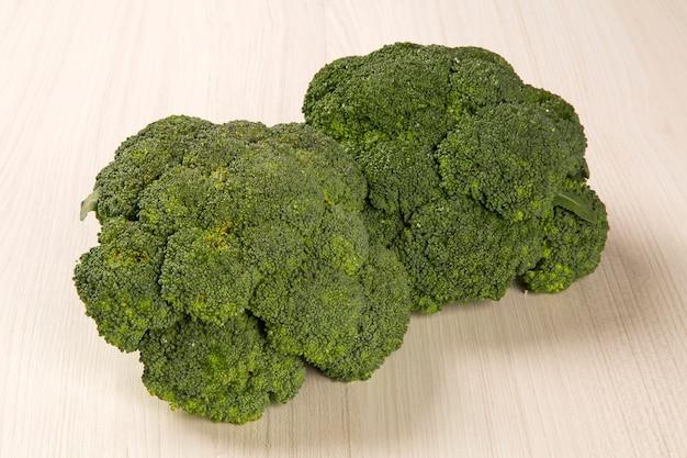 Kilka zielonych brokatów na drewnianej powierzchni. świeże warzywa