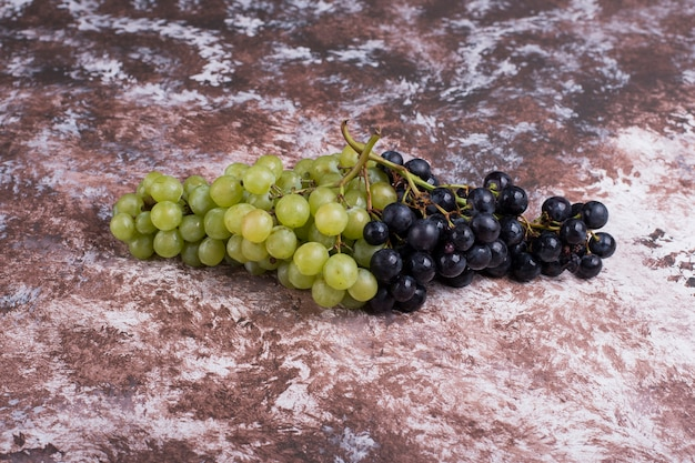 Kilka zielonych i czerwonych winogron na marmurze