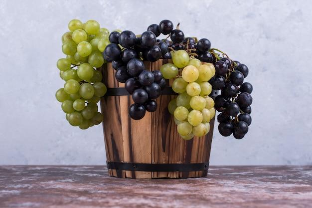Kilka zielonych i czerwonych winogron w drewnianym wiadrze na stole na niebieskiej ścianie