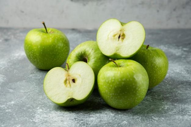 Kilka zielonych jabłek na marmurze.