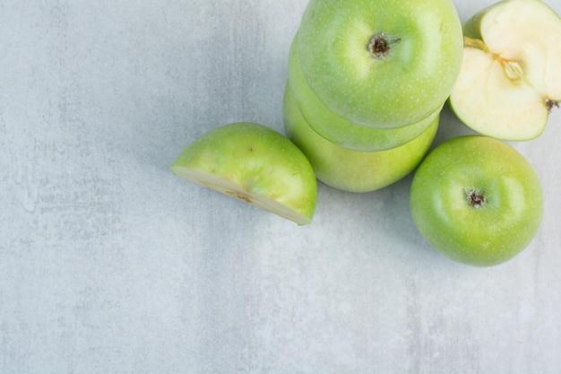 Kilka zielonych jabłek na tle kamienia. zdjęcie wysokiej jakości