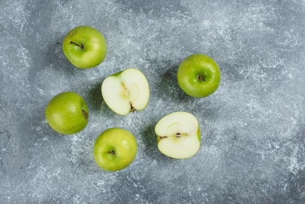 Kilka zielonych jabłek na tle marmuru.
