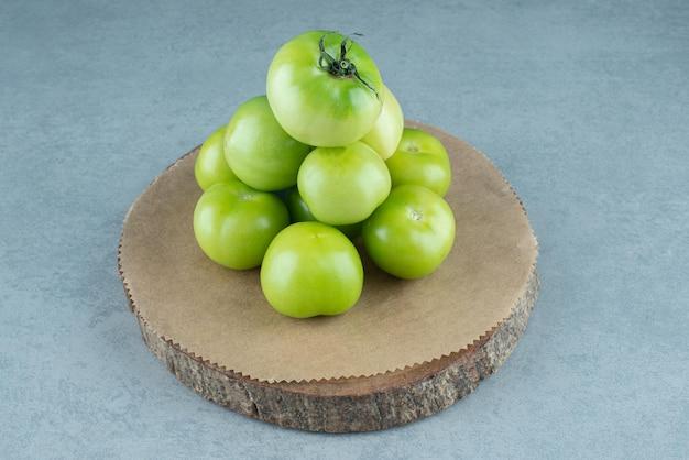 Kilka zielonych pomidorów na drewnianym kawałku.
