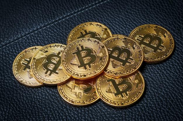 Kilka złotych monet ze znakiem bitcoin na czarnym skórzanym tle