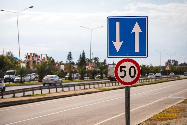 Kilka znaków drogowych: ograniczenie prędkości do 50 km na godzinę oraz regulacja ruchu na pasach na tle autostrady porośniętej drzewami