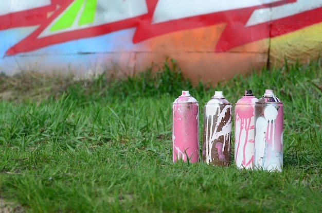 Kilka zużytych puszek z farbą leży na ziemi przy ścianie z pięknym obrazem graffiti. sztuka uliczna i wandalizm