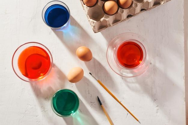 Kilkanaście jajek w kartonie, zużytych farbami akwarelowymi.
