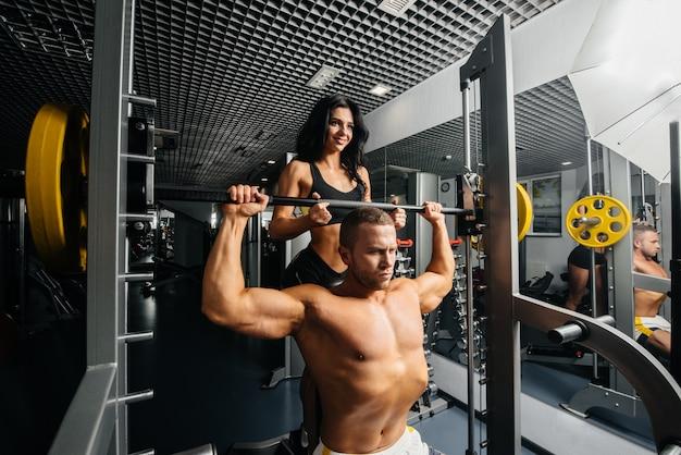 Kilku młodych sportowców angażuje się w siłownię, pomagając sobie nawzajem. fitness, kulturystyka.