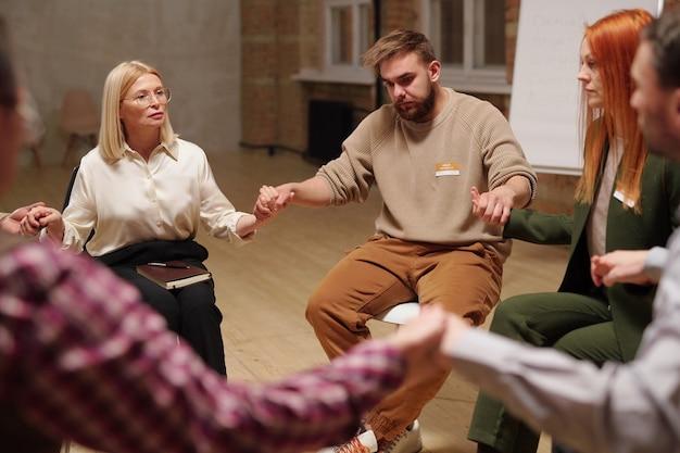 Kilku pacjentów z grupy wsparcia psychicznego i doradca trzyma się za ręce podczas sesji, siedząc w kręgu i słuchając się nawzajem