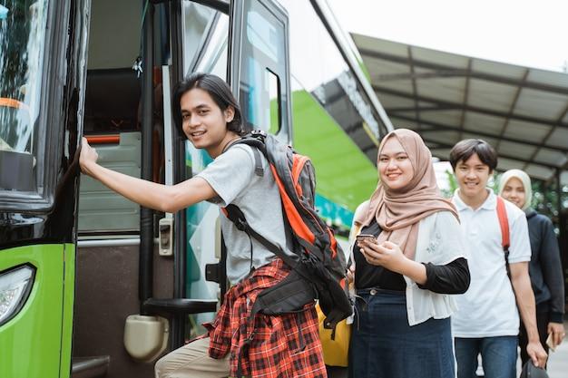 Kilku pasażerów ustawiło się równo w kolejce do autobusu