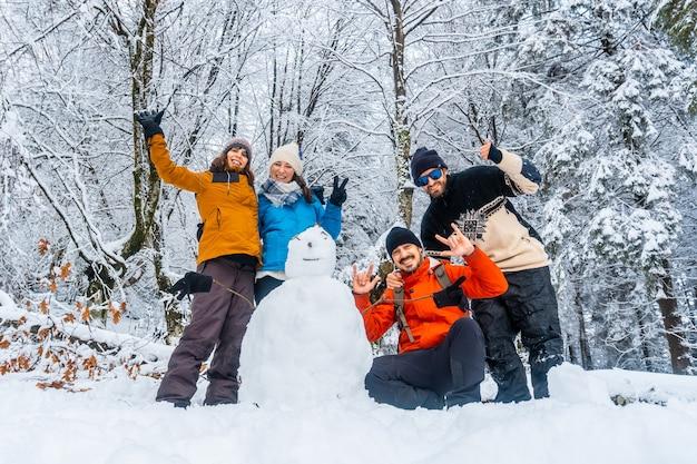 Kilku przyjaciół z bałwanem w zaśnieżonym lesie parku przyrody artikutza w oiartzun