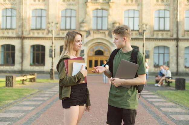 Kilku studentów stojących w pobliżu uczelni
