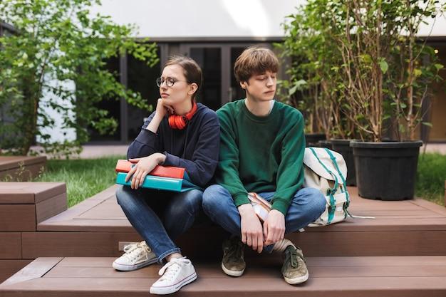 Kilku zdenerwowanych studentów siedzi z teczkami i książkami w rękach i ze smutkiem spogląda na dziedziniec uniwersytetu