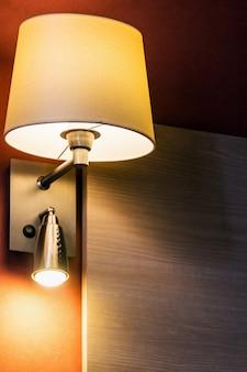 Kinkiet nad łóżkiem w pokoju lub pokoju hotelowym