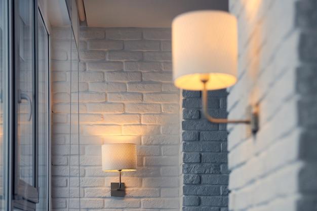 Kinkiet w nowoczesnym mieszkaniu na poddaszu. kinkiet ścienny na białym murem. żółte światła w cieniu
