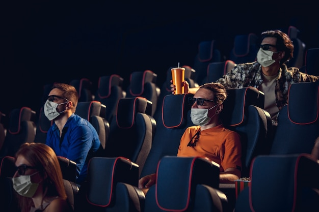 Kino w kwarantannie. zasady bezpieczeństwa podczas pandemii koronawirusa, dystans społeczny podczas oglądania filmów. mężczyźni, kobiety w masce ochronnej, siedzący w rzędach w audytorium. czas wolny, koncepcja kultury młodzieżowej.