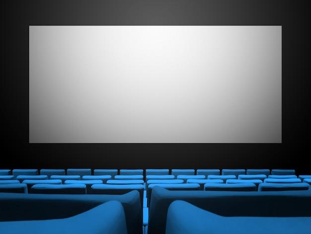 Kino z siedzeniami z niebieskiego aksamitu i pustym białym ekranem. skopiuj tło przestrzeni