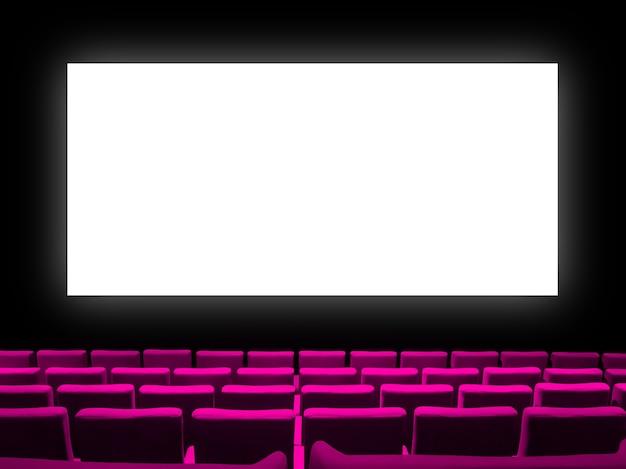 Kino z siedzeniami z różowego aksamitu i pustym białym ekranem. skopiuj tło.