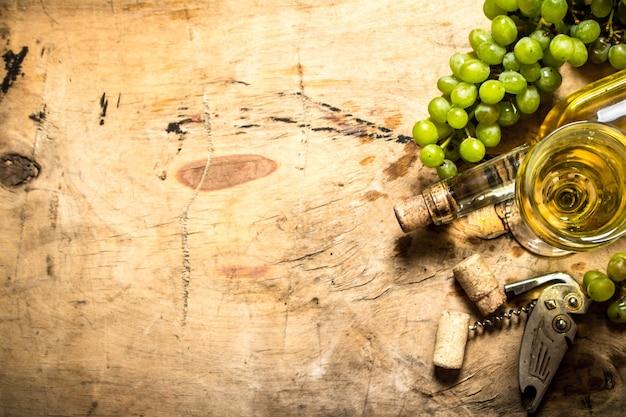 Kiść białych winogron z winem, korkociągiem i zatyczkami na drewnianym stole.