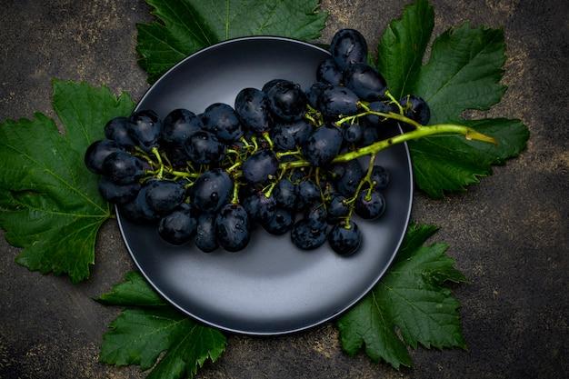 Kiść czarnych winogron na czarnym talerzu.