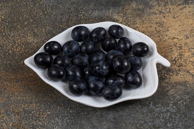 Kiść czarnych winogron na talerzu w kształcie liścia.