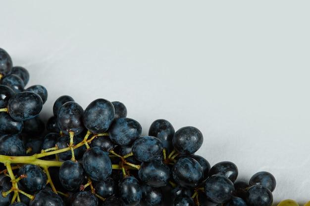 Kiść czerwonych winogron na niebieskiej przestrzeni.