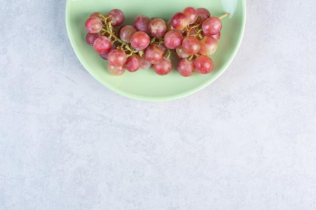Kiść czerwonych winogron na zielonym talerzu.