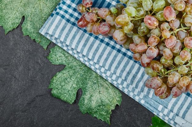 Kiść czerwonych winogron z liśćmi na ciemnym tle. wysokiej jakości zdjęcie