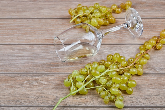 Kiść winogron i kieliszek do wina na powierzchni drewnianych