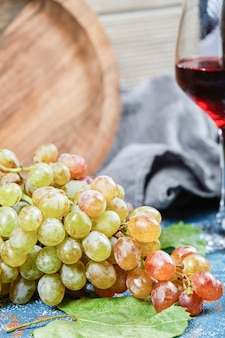Kiść winogron i kieliszek wina na niebieskim tle. wysokiej jakości zdjęcie