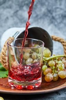 Kiść winogron i szklanka soku na marmurze.