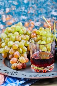 Kiść winogron i szklanka soku na niebieskim tle. wysokiej jakości zdjęcie