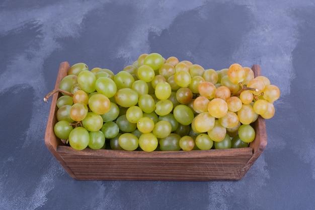 Kiść winogron w drewnianej tacy.