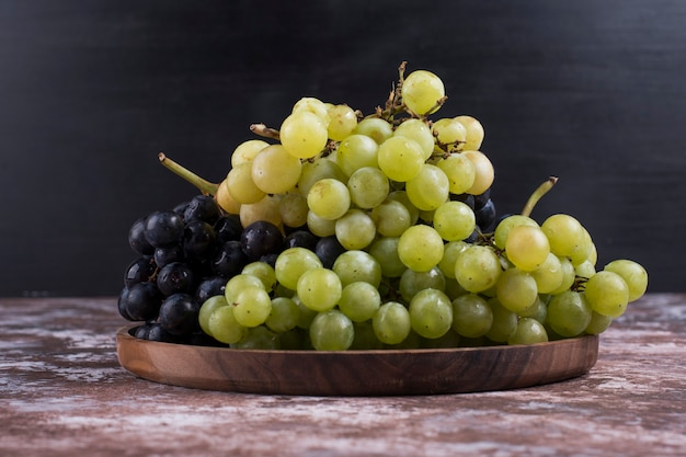 Kiść winogron zielonych i czerwonych w drewnianym talerzu na czarnym tle