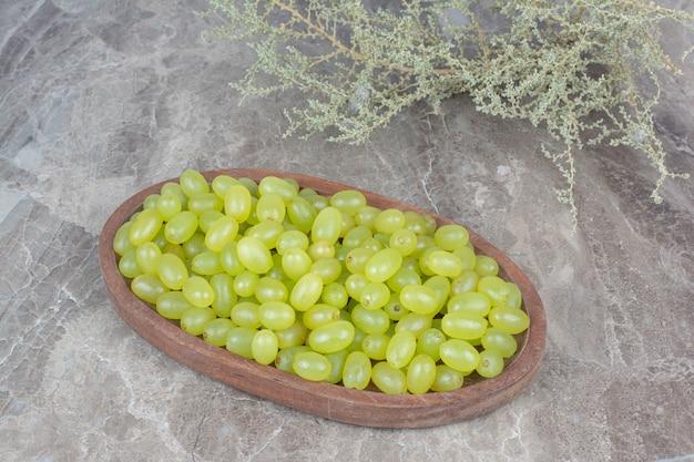 Kiść zielonych winogron w drewnianej misce.