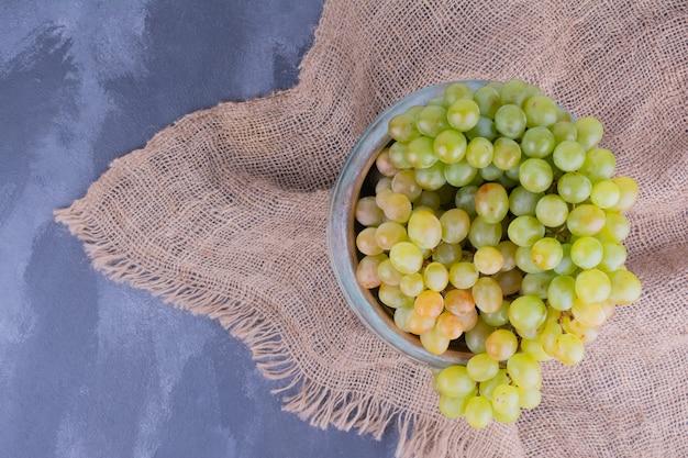 Kiść zielonych winogron w talerzu na niebiesko.