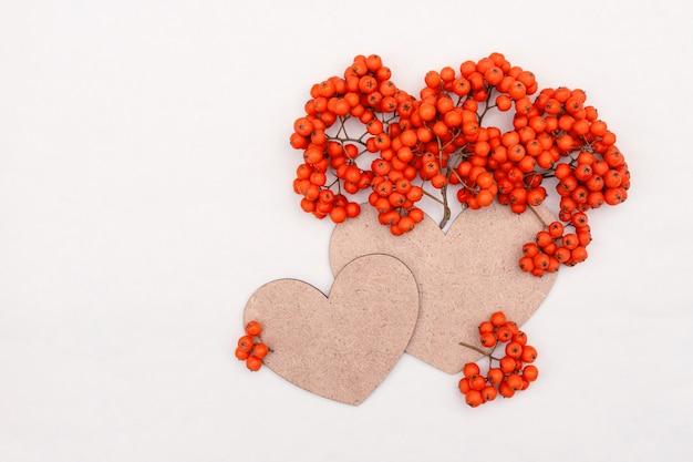 Kiście jagód jarzębiny z jasnopomarańczowymi soczystymi jagodami i sercem z miejscem na kopię