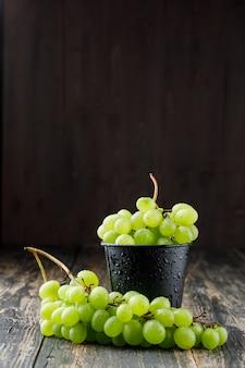 Kiście winogron w mini wiaderku na drewnianej powierzchni, widok z boku.