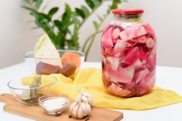 Kiszona różowa kapusta fermentacyjna z burakami i marchewką w solance w słoiku na jasnym tle.