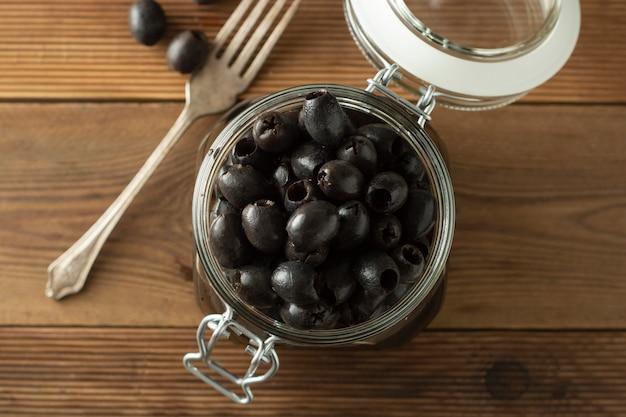 Kiszone dołkowe czarne oliwki w szklanym słoju, drewniany tło. żywność śródziemnomorska. skopiuj miejsce.