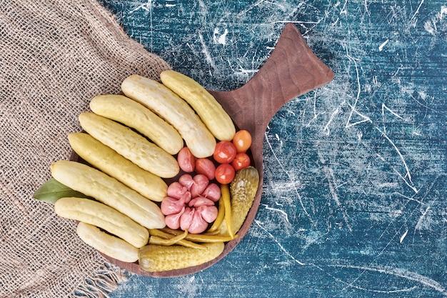 Kiszone ogórki, czosnek, papryka i pomidory na drewnianym talerzu.